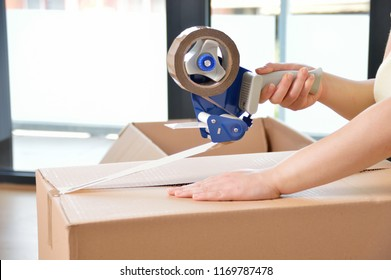 Shot of an unidentifiable young woman closing a cardboard box with tape at home