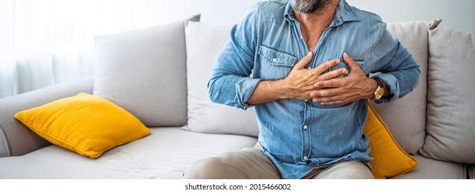 Shot of a unrecognizable man holding his chest in discomfort due to pain at home during the day. Man with chest pain suffering from heart attack while sitting at home during the day
