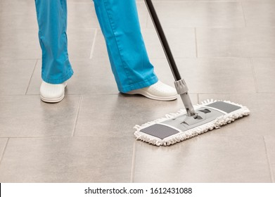 Shot of an unrecognizable woman mopping the office floor