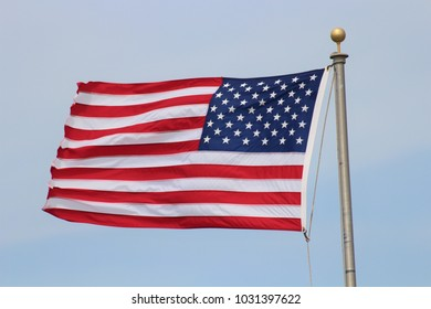 A shot of a US Flag flying in the wind on a Metal flag pole in Hutchinson Kansas.
