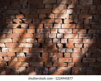 A shot of vintage red brick wall with the sunlight and shadow from the tree on the middle of the wall