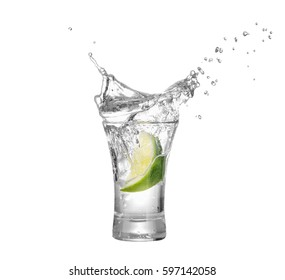 shot of vodka or tequila with lime slice and splash isolated on white background