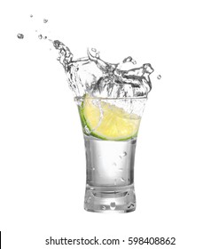 shot of vodka or tequila with lime slice and splash isolated on white background. Clipping path