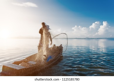 Shot of water spatter from fisherman while throwing fishing net on the lake. Fisherman with fishing net in the morning light sunshine. Stop motion of water drop.
