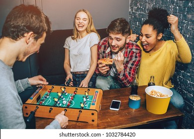 A shot where boys are playing football board game on the table while girls are cheering. Everybody is happy thinking only about the game.