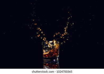 shot of whiskey with splash on black background, brandy in a glass