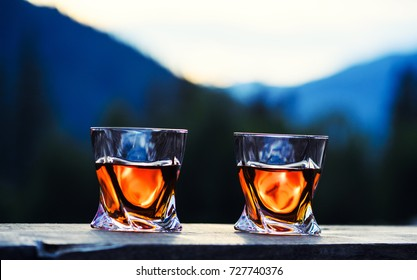 shot of whiskey at sunset dramatic sky on mountain landscape background