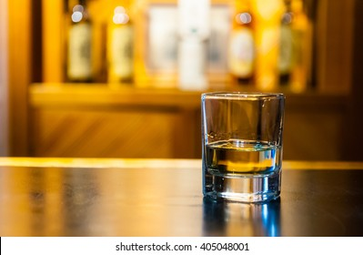 shot of whisky sitting on a bar