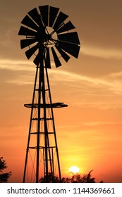A shot of a Windmill Silhouette  with bright and colorful sky and clouds. With the Sun in the evening north of Hutchinson Kansas USA.