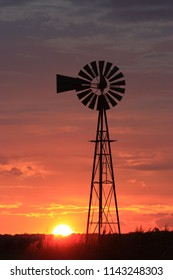 A shot of a Windmill Silhouette with a red and yellow sky that's north of Hutchinson Kansas USA.