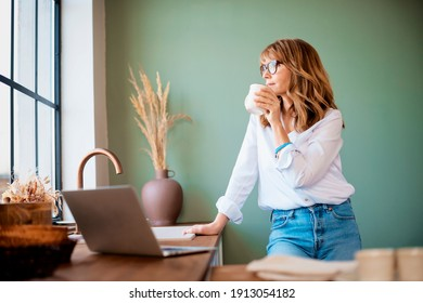 Shot of woman drinking her coffee while standing in the kitchen at home before starting working from home. Home office.