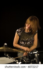 shot of woman drummer playing over black backdrop