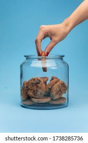 Shot of a woman hand taking cookies from a glass jar on blue background.