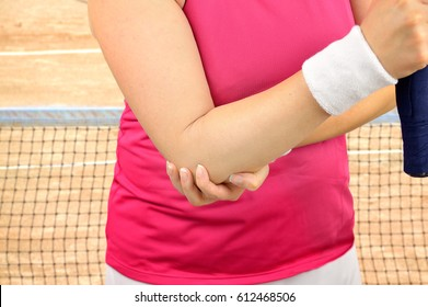 Shot of a woman tennis player with a elbow injury over on a clay court