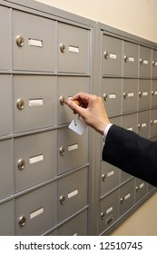 A shot of a woman unlocking a PO box.