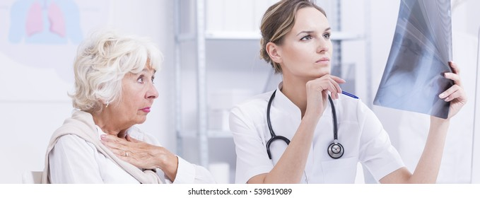 Shot of a worried senior lady waiting for a diagnosis while her young doctor profoundly looking at X-ray