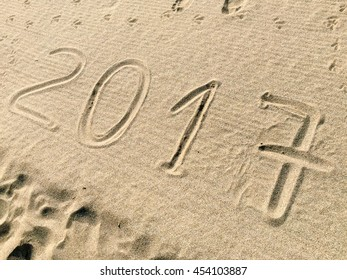 A shot of the year 2017 /numbers) engraved in the sand of a beach