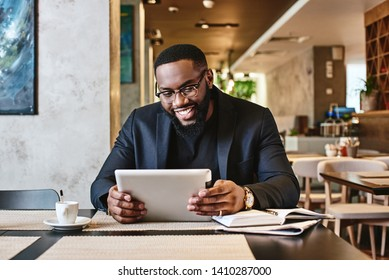 Shot of a young afro american businessman using tablet while resting in the cafe