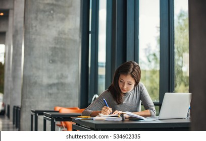 Shot of young asian female student sitting at table and writing on notebook. Young female student studying in library.