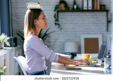 Shot of young attractive woman at the desk with books on her head while working with computer at home.