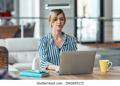 Shot of young attractive woman at the desk with books on her head while working with computer in living room at home.
