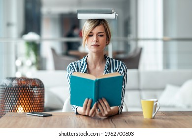 Shot of young attractive woman at the desk with books on her head while reading a book in living room at home.