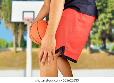 shot of a young basketball player with an inflamed knee at outdoors