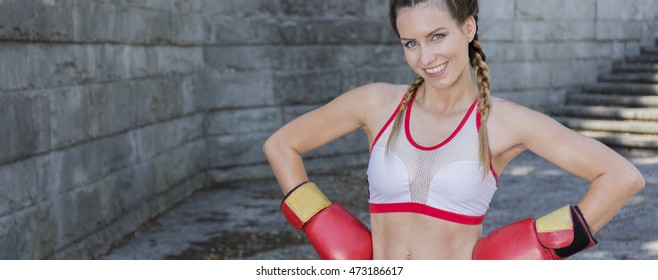 Shot of a young beautiful boxer posing against a concrete wall