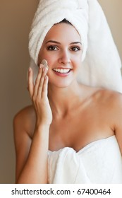 A shot of a young beautiful woman applying lotion to her face