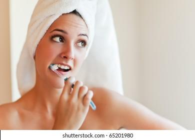 A shot of a young beautiful woman brushing her teeth