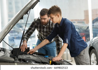Shot of a young boy talking to his cheerful father sitting together in a new car driving travelling trip journey happiness lifestyle parent vehicle automobile rent safety insurance family parenting