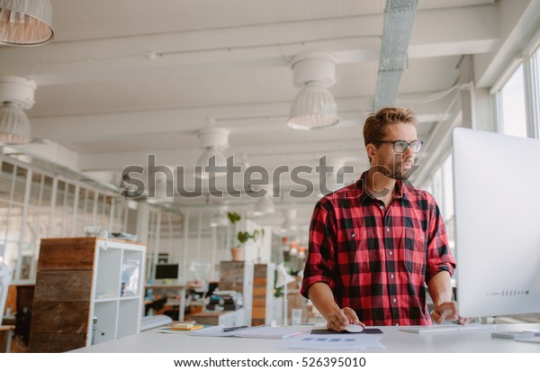 Shot of young businessman in casual clothes at modern startup business office space, working on  desktop computer.