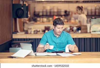 Shot of a young businessman doing books at a table during a late night in his restaurant. Young startup owner looking worried while looking over the papers at the final fiscal year.