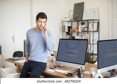 Shot of a young businessman talking with somebody while sitting at office.
