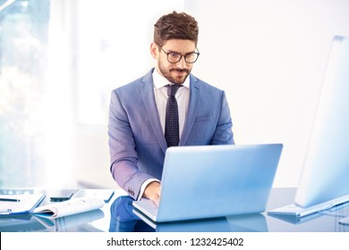 Shot of young businessman wearing suit while sitting in front of laptop and working on business project.