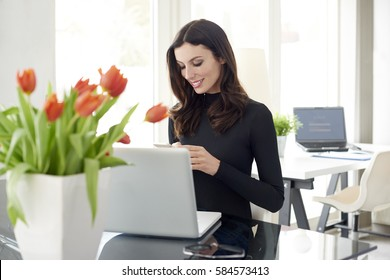 Shot of a young businesswoman send text message on her cellphone while sitting at office in front of laptop.
