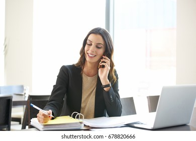 Shot of a young businesswoman sitting at office desk in front of laptop and making call while considering the possibilities with her client.