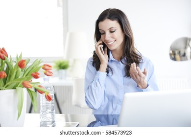 Shot of a young businesswoman talking with somebody on her mobile phone while working on laptop in the office.