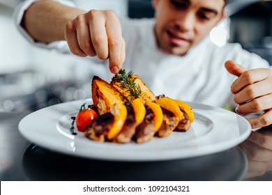 Shot of a young chef decorating meal in the kitchen