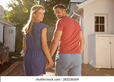 Shot of young couple in backyard on a bright sunny day. They are walking to their house hand in hand, looking over their shoulders at the camera.