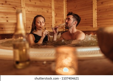 Shot of a young couple drinking champagne in a jacuzzi