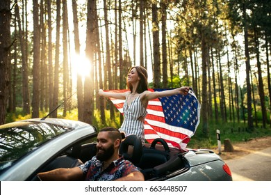 Shot of a young couple enjoying riding in a car. Focus on the woman who is holding an american flag.