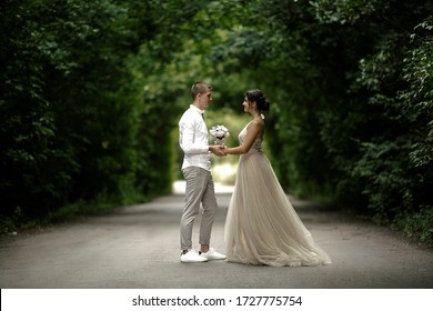Shot of young couple in love standing opposite each other on the middle of the road against tree tunnel. Happy woman bride in long beautiful dress holding hands looking at each other. Tunnel of love