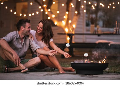 Shot of a young couple roasting marshmallows over barbecue