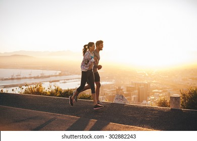 Shot of young couple running on hillside road outside the city.  Young man and woman jogging in morning with bright sunlight.