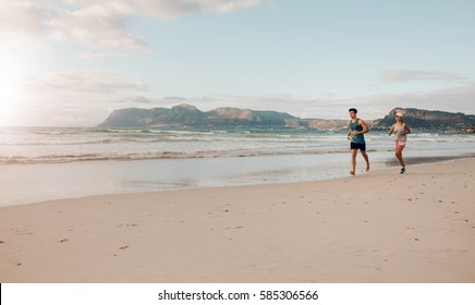 Shot of young couple running together on the sea coast in morning. Morning run on the beach