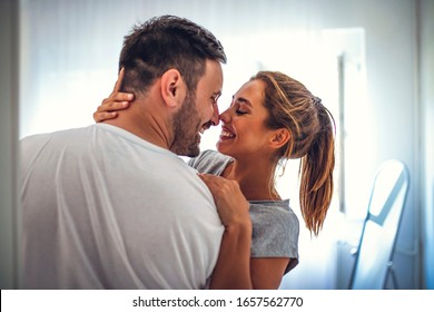 Shot of a young couple sharing an intimate moment in their bedroom. Couple on Valentine day enjoy in love. They are in bedroom and having romantic moment together