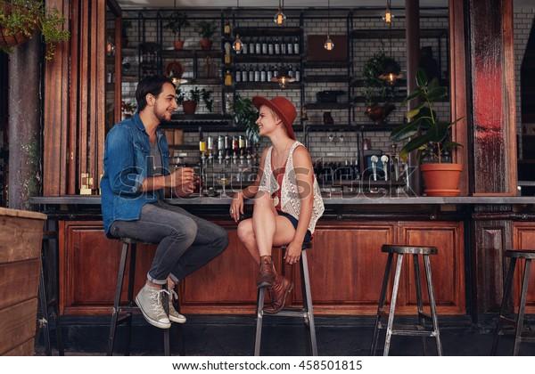 カフェのカウンターに座っている若い夫婦の写真。喫茶店の若い男女。