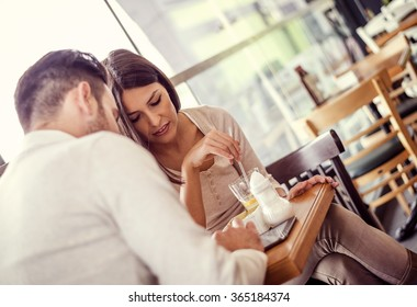 Shot of a young couple sitting with a tablet while on a coffee date