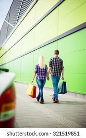 A shot of a young couple with their shopping bags. Selective focus.